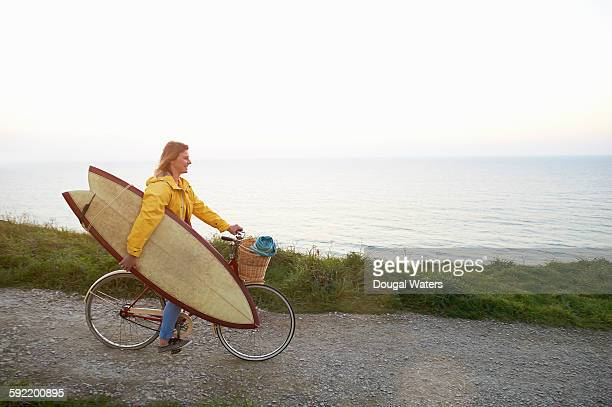 Surfer riding bicycle whilst carrying surf board.