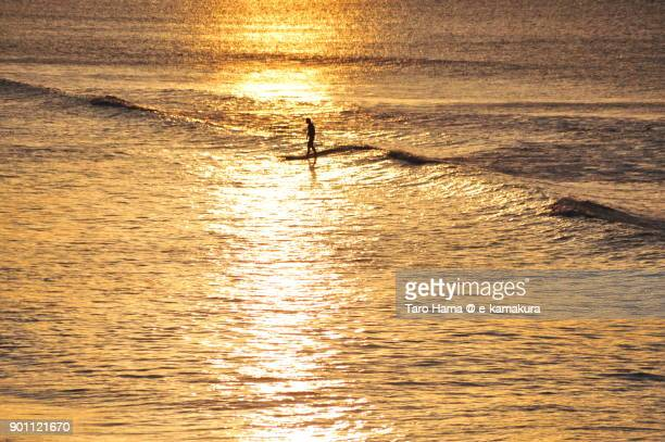A surfer riding on morning wave in Kamakura city in Kanagawa prefecture in Japan