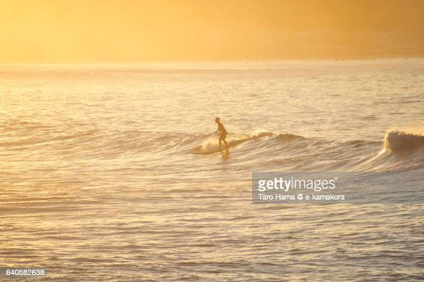 A surfer riding on the morning wave