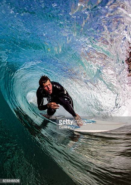 surfer riding through tube wave - サーフィン ストックフォトと画像