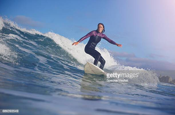 surfer riding wave at sunrise - wetsuit stock pictures, royalty-free photos & images