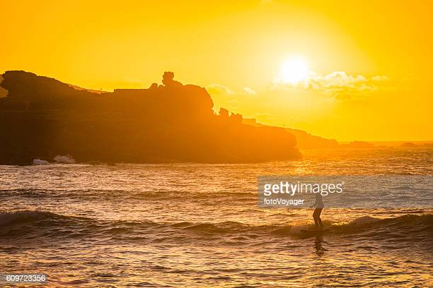surfer riding waves at golden sunset beach st ives cornwall - st. ives cornwall stock pictures, royalty-free photos & images