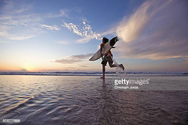 Surfer running into the ocean