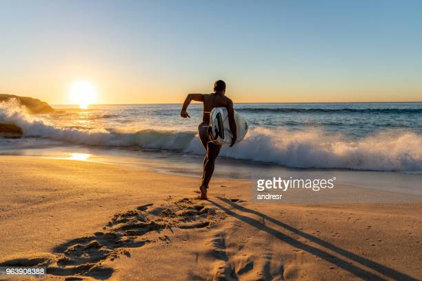 surfer running into the water carrying his board - breaking wave stock pictures, royalty-free photos & images