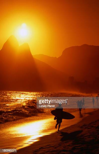 Surfer running on Ipanema Beach at sunset.