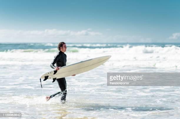 surfeur courant sur la plage - queensland photos et images de collection