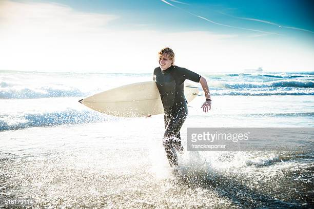 surfer running on the beach