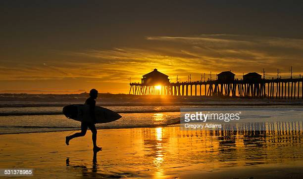 Surfer Running to Catch the Waves at Sunset