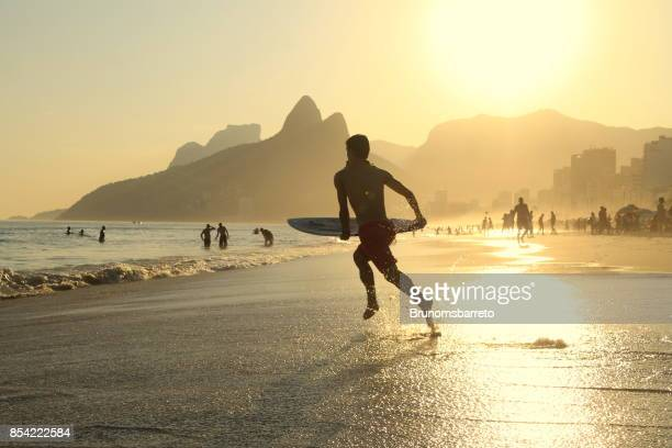 surfer running to the sea - rio de janeiro imagens e fotografias de stock