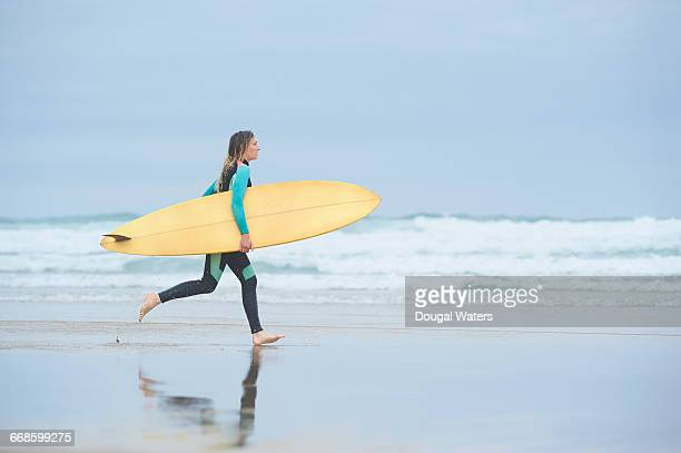 Surfer running with board along beach.