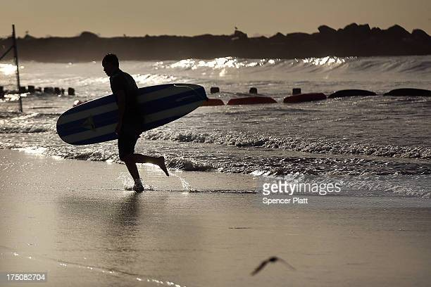 A surfer runs out of the water after an early morning session at Rockaway Beach on July 31 2013 in the Queens borough of New York City Despite the...