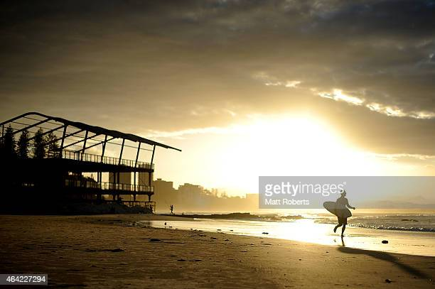 A surfer runs up the beach as the sunset at Snapper Rocks on February 16 2015 on the Gold Coast Australia