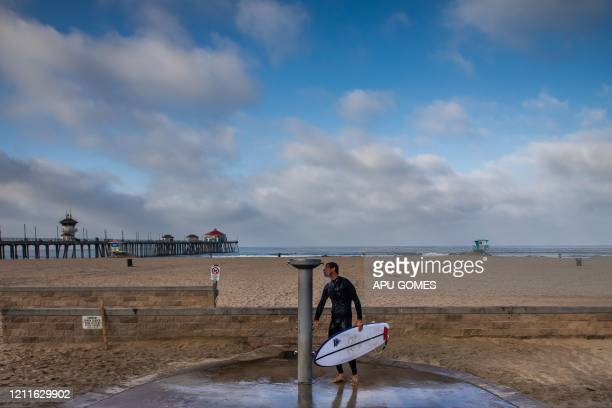A surfer showers after leaving the ocean in Huntington Beach California on May 02 2020 Orange County beaches will remain closed after a California...