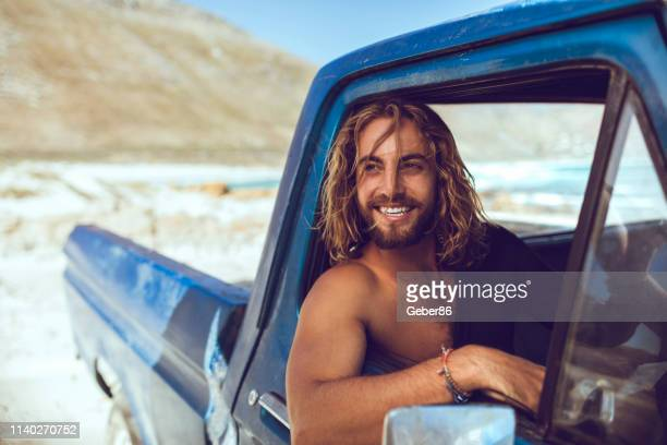 surfer sitting in car - masculinity stock pictures, royalty-free photos & images