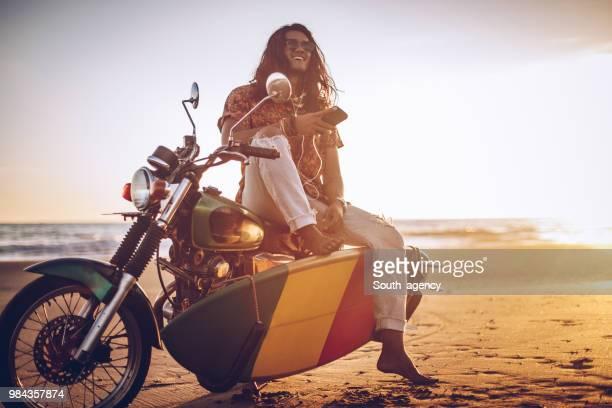 ビーチでバイクの上に座ってサーファー - のりものに乗る ストックフォトと画像
