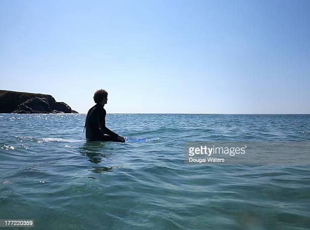 Surfer sitting on surfboard at sea.