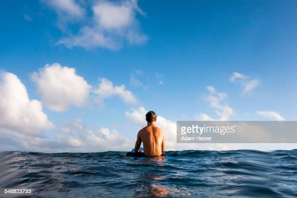 Surfer sitting on surfboard in ocean