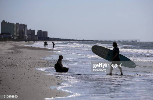 A surfer speaks with a person sitting on the shore in Cherry Grove Beach South Carolina US on Wednesday April 22 2020 Governor Henry McMaster said he...