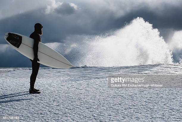 Surfer standing by Lake Ontario in winter