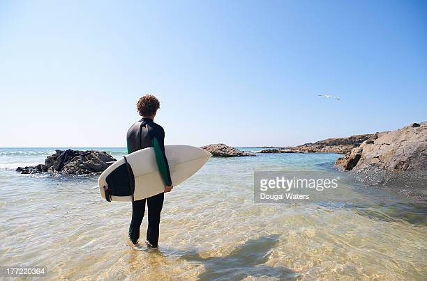 Surfer standing in sea with board.