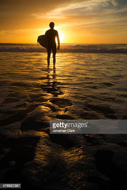Surfer standing in the water at sunset