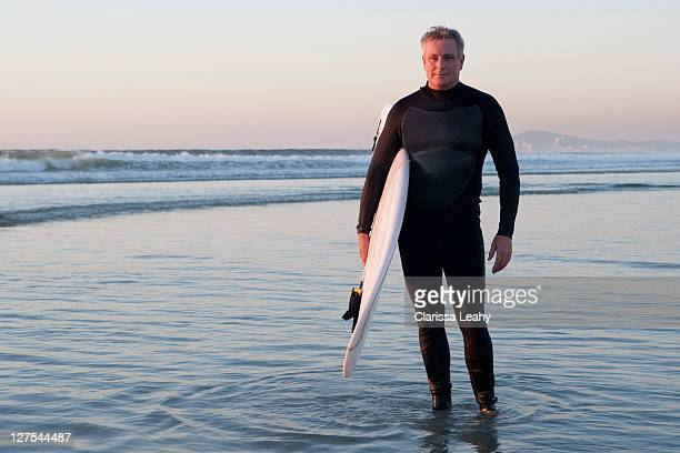surfer standing in water - wading stock pictures, royalty-free photos & images