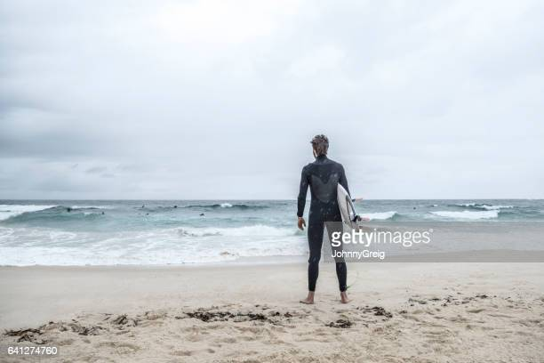 Surfer standing on beach looking out towards the sea, rear view