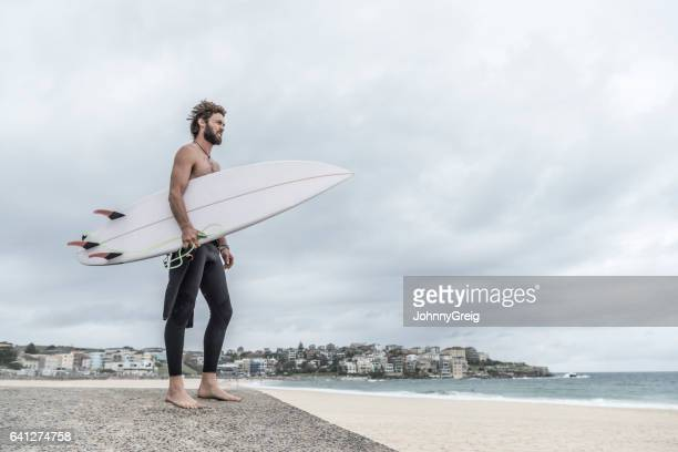 海を見渡すサーフボードとビーチに立っているサーファー