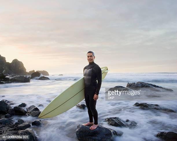 Surfer standing on rock in ocean, portrait
