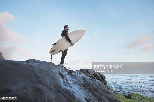 surfer standing on rock - surfboard stock pictures, royalty-free photos & images