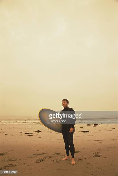 Surfer standing on sepia beach