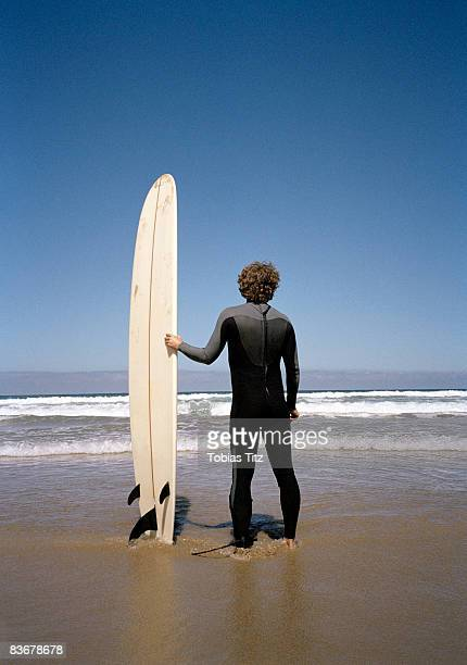 A surfer standing on the beach with his surfboard watching the ocean