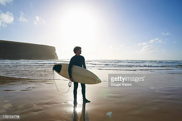 Surfer standing with board at beach.