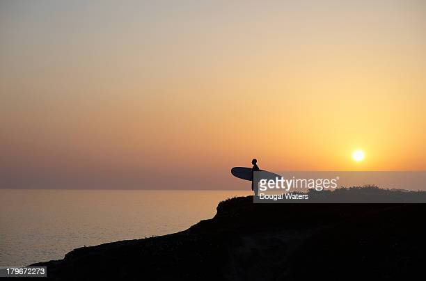 Surfer standing with board at sunset.