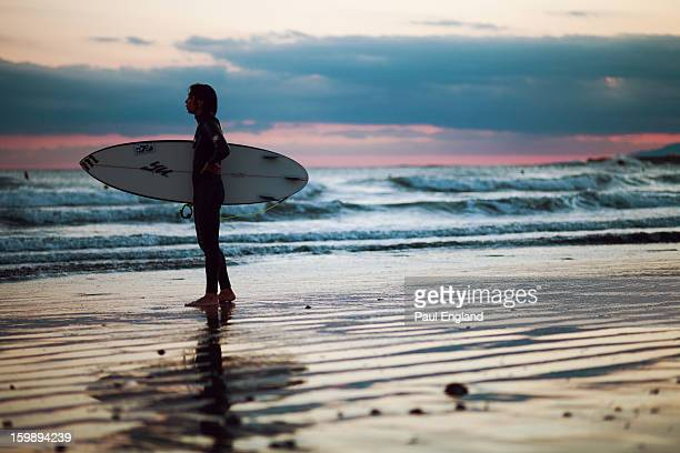 Surfer stands on the beach at sunset in Kamakura