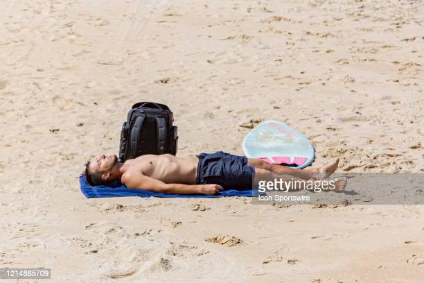 A surfer sunbathes along the shoreline on Memorial Day weekend on May 22 in Virginia Beach VA This is the first day of the beach's reopening for...