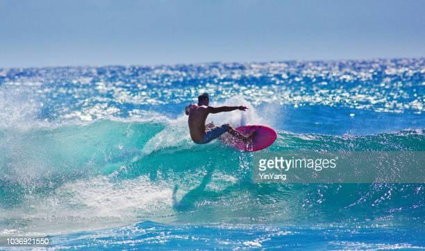 surfer surfing in poipu beach, kauai,hawaii - kauai stock pictures, royalty-free photos & images