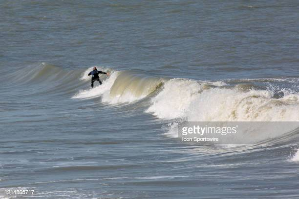 A surfer takes advantage of the rough waves left behind by Tropical Storm Arthur on May 22 in Virginia Beach VA This is the first day of the beach's...