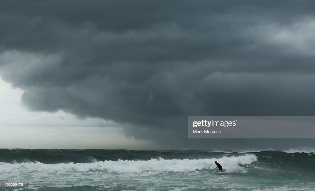 A surfer takes on the large swells as storm clouds gather at Coogee Beach after winds and rain battered Sydney last night on January 29, 2013 in Sydney, Australia. Parts of Sydney are experienced record rainfall after ex-cyclone Oswald swept through the city last night.