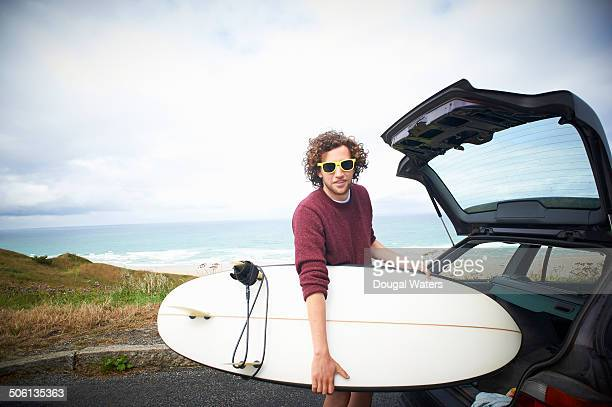 Surfer taking surfboard out of car