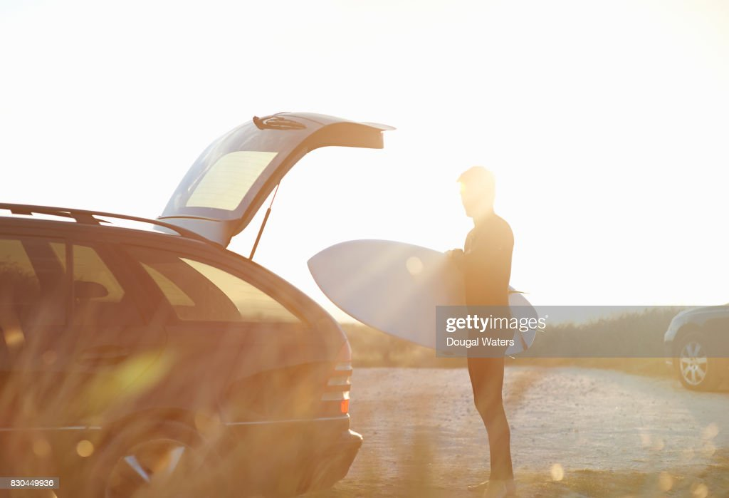 Surfer taking surfboard out of car. : Stock Photo