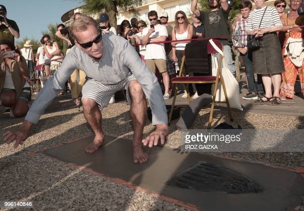 US surfer Tom Curren leaves his footprint cement slab as he takes part in the inauguration of the Anglet Surf Avenue with other surfers from all over...