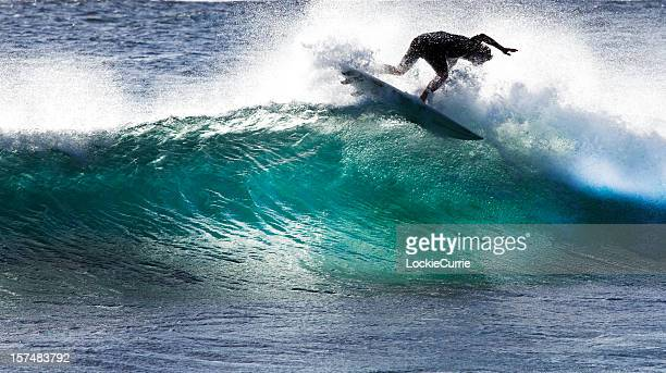 A surfer tries to stay on the surfboard while riding a wave