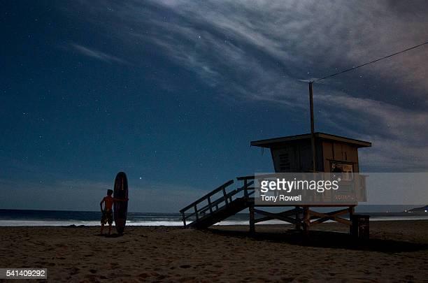 Surfer under stars at Zuma Beach Lifegard Station, Malibu, California