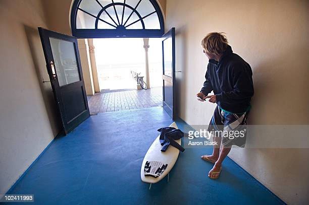 Surfer using smart phone standing in a hall near beach