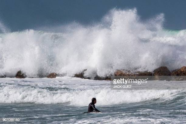 A surfer wades into the water as waves break against the shore during a winter storm in the Mediterranean coastal town of Netanya north of Tel Aviv...