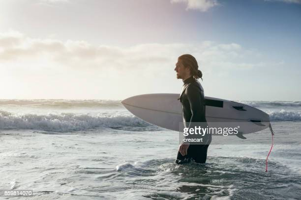 surfer wading into the sea, fistral beach, newquay, cornwall. - surf stock pictures, royalty-free photos & images
