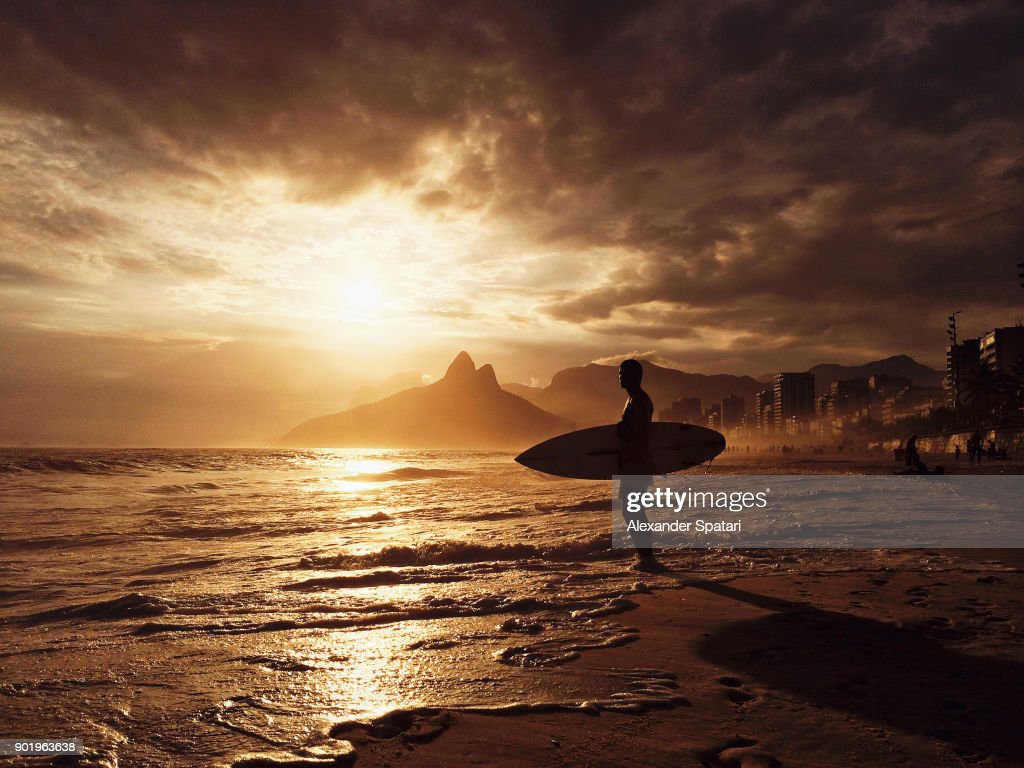 Surfer waiting for a wave during sunset at Ipanema Beach, Rio de Janeiro, Brazil : Stock Photo