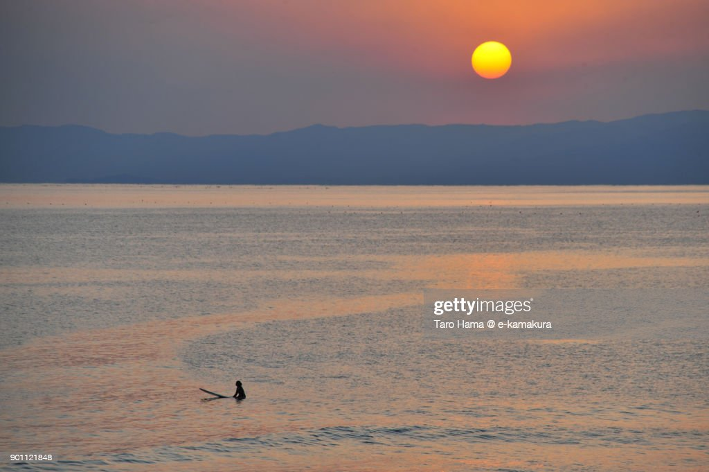A surfer waiting for next wave and evening sun on Izu Peninsula and Sagami Bay in Kanagawa prefecture in Japan : ストックフォト
