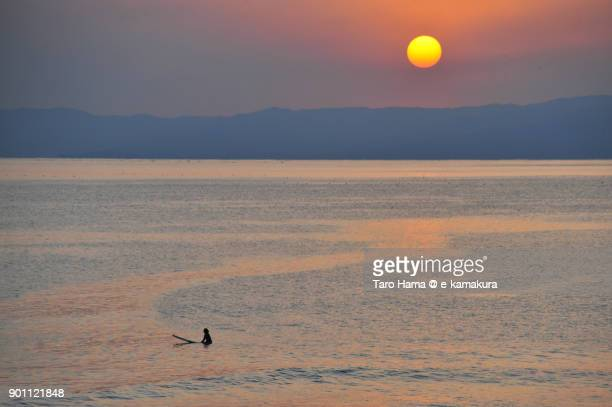 A surfer waiting for next wave and evening sun on Izu Peninsula and Sagami Bay in Kanagawa prefecture in Japan